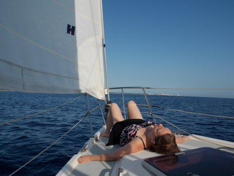 Photo of Jennifer doing Constructive Rest on the bow of a sail boat on the Mediterranean Sea